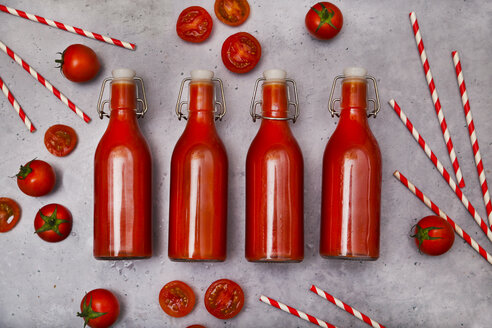 Row of four swing top bottle of homemade tomato juice, straws and tomatoes on grey ground - RTBF01268