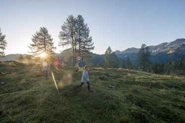 Family hiking in alpine meadow at sunset - HHF05557