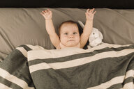 Portrait of baby girl lying in bed with arms raised, overhead view - CUF02782