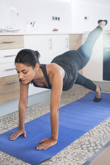 Woman doing exercise on mat on kitchen floor - CUF02788