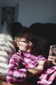 Girl relaxing on sofa, looking at smartphone - CUF02791