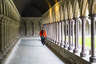 Female tourist strolling in Abbey cloister of Mont Saint-Michel, France - CUF02917