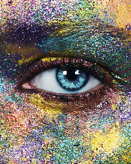 Studio portrait of blue eyed young woman with glittery multi coloured powder on face, close up of eye - CUF02953