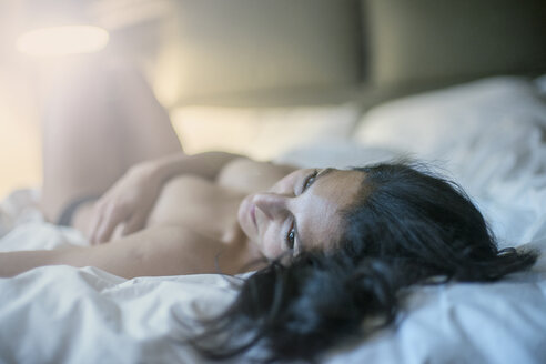 Nude woman lying on bed looking away - CUF02956