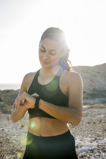 Young female runner checking smartwatch near coast, Las Palmas, Canary Islands, Spain - CUF02971