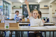Schoolgirl with hand raised in classroom at primary school - CUF03064