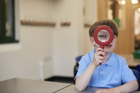Schoolboy looking through magnifying glass in classroom at primary school, portrait - CUF03073