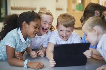 Schoolboys and girls laughing at digital tablet in classroom at primary school - CUF03076