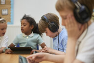 Schoolboys and girl listening to headphones in class at primary school - CUF03085