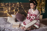 Young woman sitting on bed, wearing christmas jumper, thoughtful expression - CUF03124