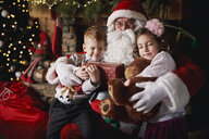 Young girl and boy visiting Santa, holding gifts - CUF03127