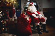 Portrait of Santa Claus, sitting in chair with sack full of presents - CUF03136