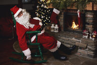 Santa Claus, sleeping in chair beside fireplace - CUF03139