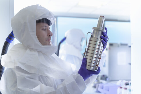 Scientist in protective wear inspecting filter in laboratory - CUF03220