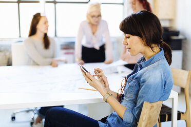 Four women in business meeting, woman in foreground using smartphone - CUF03226