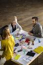 Male and female designers discussing colour swatches on design studio table - CUF03268