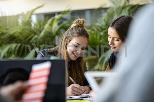 Female designers making notes at design studio desk, over shoulder view - CUF03277