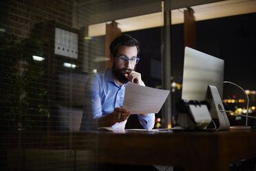 Young businessman reading paperwork at office desk at night - CUF03298