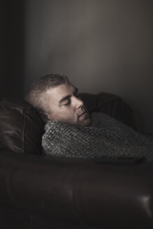 Mature man wrapped in blanket asleep on armchair - CUF03316