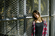 Portrait of beautiful young woman leaning against a fence - JRFF01630