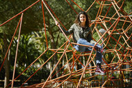 Portrait of young woman on a climbing frame on a playground - JRFF01639