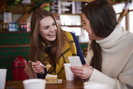 Young women smiling over text message on mobile phone - CUF03475