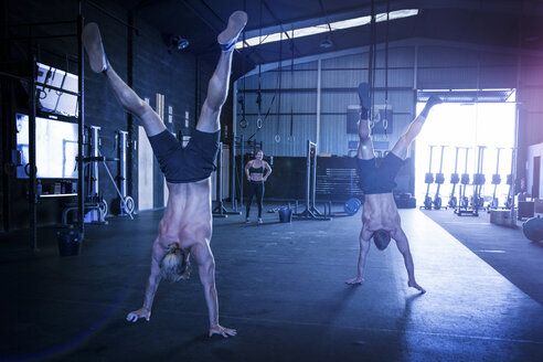 Three people exercising in gym, two men doing handstand walks - CUF03481