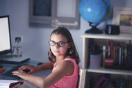 Portrait of young girl wearing glasses, sitting at desk, using computer - CUF03511