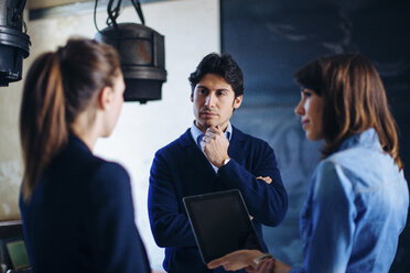Three businesspeople standing in meeting room, businesswoman holding digital tablet - CUF03523