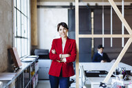 Portrait of businesswoman in office, arms folded, smiling, male colleague working in background - CUF03526