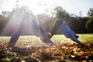 Two women doing yoga in park on autumn day - CUF03610