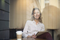 Mid adult woman in cafe window seat using digital tablet - CUF03625