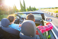 Rear view of couple driving convertible on sunlit rural road, Majorca, Spain - CUF03643