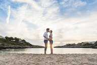 Pregnant woman and man standing face to face on beach, kissing - CUF03664