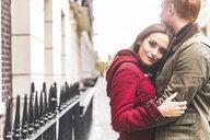 Couple hugging on street, London, UK - CUF03691