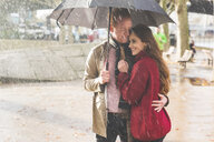 Couple with umbrella, standing under rain in park, London, UK - CUF03697
