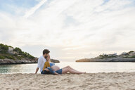 Pregnant woman and man relaxing together on beach - CUF03706