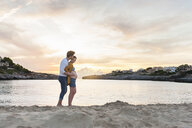Pregnant woman and man, standing together on beach, man touching woman's stomach - CUF03709