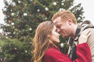 Couple hugging in front of Christmas tree - CUF03721