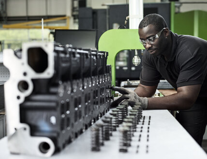 Worker in metalworking factory loading cylinder head - CVF00463
