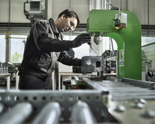 Worker in metalworking factory loading cylinder head - CVF00466