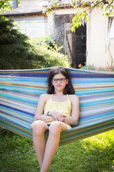 Portrait of smiling girl sitting on a hammock in the garden - LVF06959