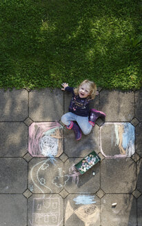 Smiling little girl drawing with chalk outdoors, top view - LHF00566