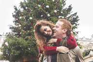 Couple playing piggyback in front of Christmas tree - CUF03734
