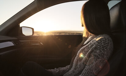 Young woman sitting in passenger seat of car, looking out of window - CUF03812