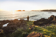 Woman watching sunset from coast, Pacific Rim National Park, Vancouver Island, British Columbia, Canada - CUF03854
