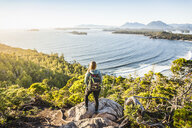Elevated view of female hiker looking out from coastal forest, Pacific Rim National Park, Vancouver Island, British Columbia, Canada - CUF03857