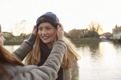 Young woman putting knitted hat on friend, outdoors, smiling - CUF03935