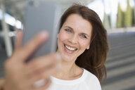 Businesswoman taking smartphone selfie outside airport - CUF03962