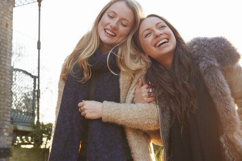 Two female friends outdoors, walking arm in arm, laughing - CUF04001